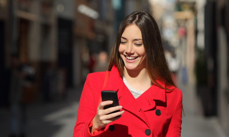 37189550 - happy woman using a smart phone while is walking in the street in a sunny day